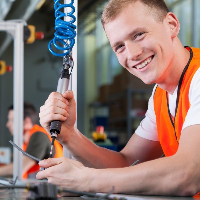 Young smiling man working on the production line